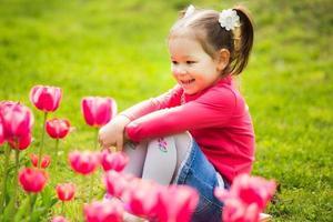 glad liten flicka som sitter i gräset och tittar på tulpaner