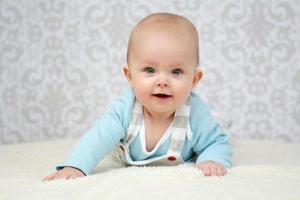 baby flicka med blå ögon tittar på kameran foto