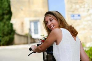 glad och attraktiv ung kvinna som cyklar på sommaren foto