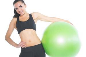 glad brunett kvinna poserar håller en grön träningsboll foto