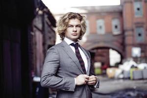 ung affärsman i en grå kostym, affärsstil, porträtt på foto