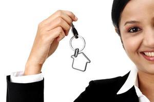 glad affärskvinna innehav hus nyckel