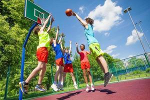 barn hoppar för boll under basketspel foto
