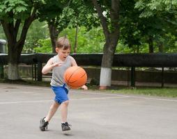 ung pojke som spelar basket foto