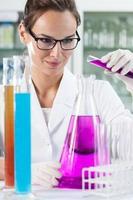 kvinna gör experiment i laboratorium foto