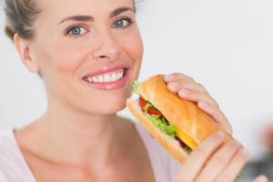 glad kvinna som håller smörgås foto