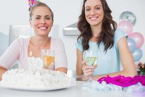 glada kvinnor med födelsedagstårta foto