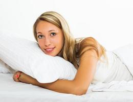 glad kvinna som ligger på sängen foto