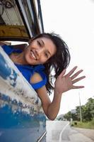 glad tjej som vinkar från bussen foto