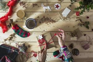 kvinna som dekorerar en julklapp, omgiven av festlig deco foto