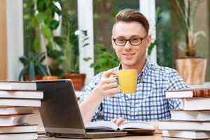 ung student som arbetar i ett bibliotek foto
