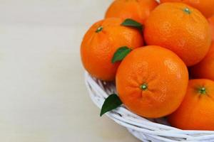 mandariner i vit rottingkorg med kopieringsutrymme foto