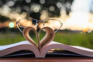 närbild bok och glasögon på bordet under solnedgången tid foto