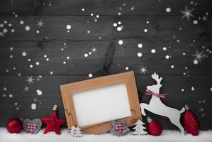 grått julkort med röd dekoration, kopieringsutrymme, snöfallar foto
