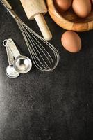 köksredskap och bakningsingredienser på svart bakgrund, kopieringsutrymme. foto