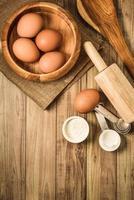 köksredskap och bakningsingredienser på träbakgrund, kopieringsutrymme. foto