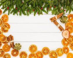 julgran, torkade apelsiner, kanel, vit träbakgrund, kopieringsutrymme. foto
