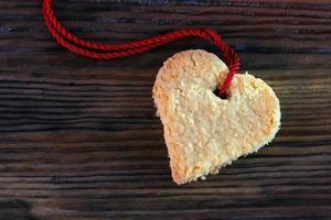 hjärtkaka med band på mörkt gammalt trä, kopieringsutrymme foto