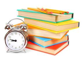 väckarklocka och flerfärgade böcker. foto