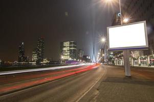 vit skylt på sidan av en trafikerad väg foto