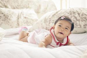 glad baby flicka på sängen foto