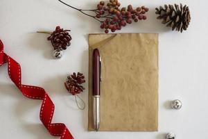 gammalt papper, rött band och julgranskulor foto