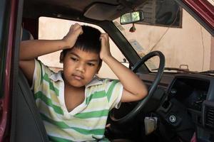 pojke ledsen ensam i den gamla bilen foto