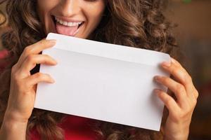 närbild på glad ung kvinna som slickar kuvert foto