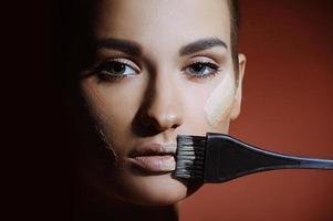 vacker flicka med ren hud som applicerar kvinnlig sminkkräm foto
