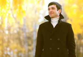 porträtt leende man i kappa utomhus höst park foto