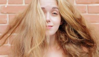 attraktiv ung blondin på bakgrunden av en tegelvägg. foto