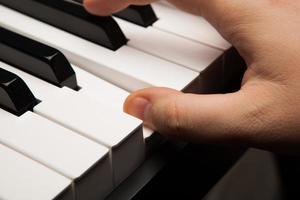pianotangenter och mänskligt finger foto