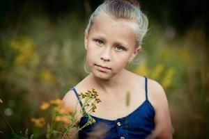 vacker liten flicka på en äng foto