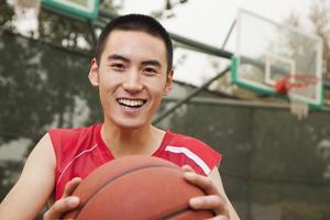 ung man sitter med en basket, porträtt foto