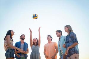 glada vänner som kastar volleyboll foto