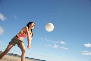 tonårsflicka som spelar beachvolleyboll foto