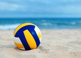 bollen ligger på sand nära havet foto