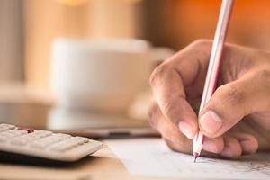 mänsklig hand med penna beräknar budget. tekopp och digitalt bord foto