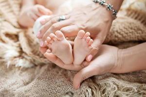 baby fötter i mamma händer. lycklig familj koncept. foto