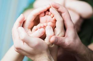 baby fötter på föräldrarnas händer foto