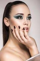 vacker flicka med gröna smokey-ögon sminkar foto