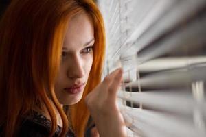 vacker flicka tittar genom persienner foto