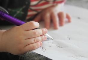 litet barns hand skriva i anteckningsboken foto