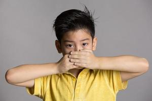 ung asiatisk pojke med båda händerna som stänger munnen foto