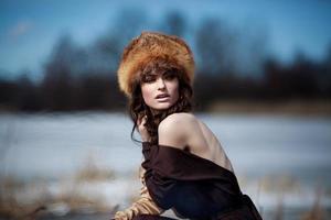 porträtt av en vacker leende flicka i en pälshatt foto