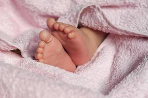 baby fötter under filt foto