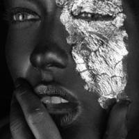 mode porträtt av mörkhyad tjej med silverfolie smink. foto