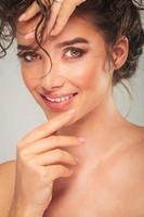 porträtt av vacker modell vidrörande ansikte och fixa hår