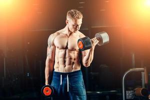 idrottsman muskulös kroppsbyggare tränar tillbaka med hantel i gymmet foto