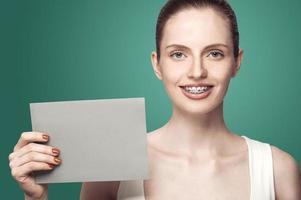 vacker flicka med hängslen och grått kort i händerna foto